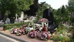une tombe dans un cimetire avec des gerbes et couronnes de fleurs déposé lors d'un décès