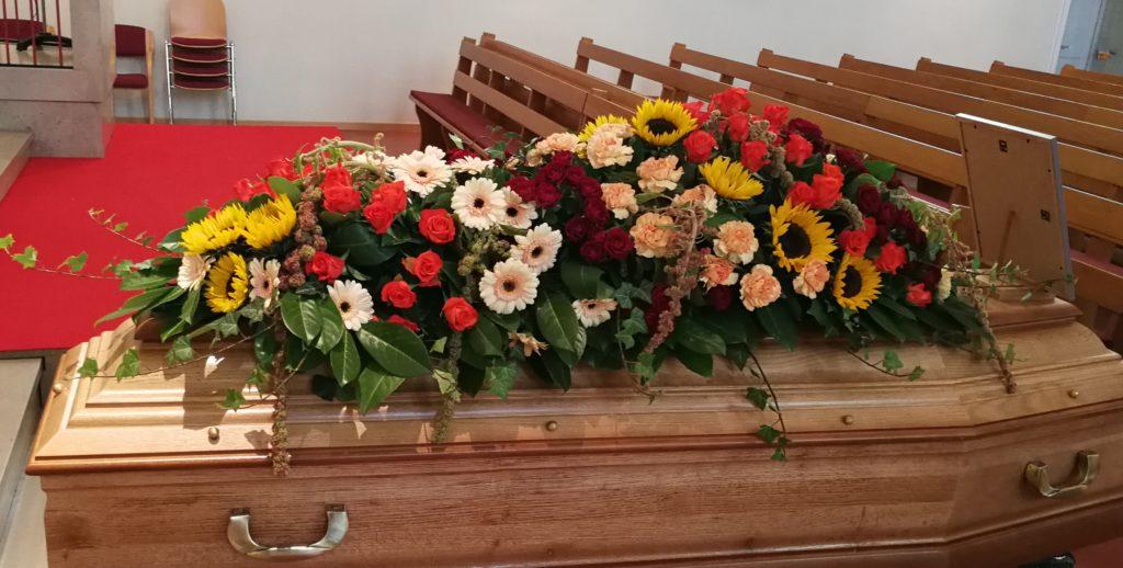 dessus de cercueil en fleurs fraiches, avec des tournesol, rose rouge et orange, germini et oeillet couleur pèche